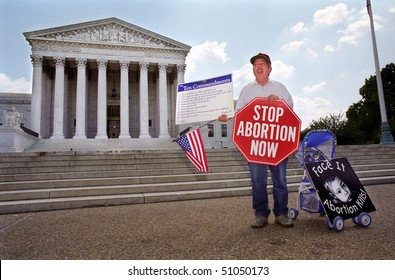 WASHINGTON, DC - MAY 14: An anti-abortion protester holds a stop sign and the Ten Commandments on the sidewalk in front of the U.S. Supreme Court on May 14, 2001 in Washington, D.C.