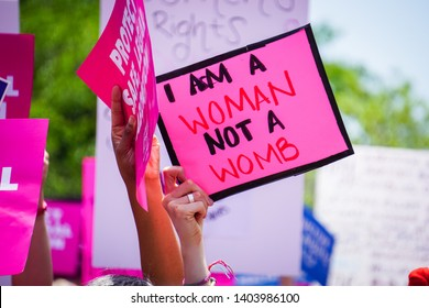 "WASHINGTON, DC - MAY 21, 2019: A woman holds a sign that says ""I am a woman not a womb"" to protest abortion bans"