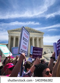 "WASHINGTON, DC - MAY 21, 2019: A woman holds a sign that says ""If it's not your body it's not your choice"" in front of the Supreme Court"