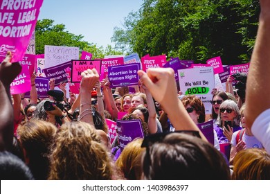 WASHINGTON, DC - MAY 21, 2019: A crowd of women raise their fists supporting reproductive justice at the #StopTheBans rally in DC