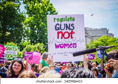 "WASHINGTON, DC - MAY 21, 2019: A woman holds a sign that says ""regulate guns not women"" to protest abortion bans"