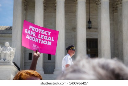 "WASHINGTON, DC - MAY 21, 2019: A woman holds a sign that says ""Protect safe, legal abortion"" in front of the Supreme Court"