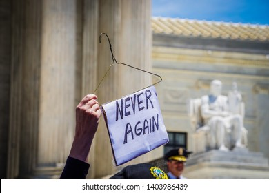 "WASHINGTON, DC - MAY 21, 2019: A woman holds a wire hanger with a sign that says ""Never Again"" in front of the Supreme Court"