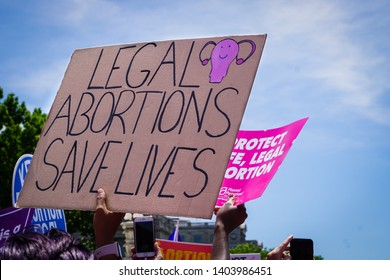 "WASHINGTON, DC - MAY 21, 2019: A woman holds a sign that says ""Legal abortions save lives"" to protest abortion bans"