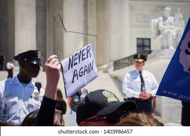 "WASHINGTON, DC - MAY 21, 2019: A woman holds a wire hanger with a sign that says ""Never Again"" in front of the Supreme Court while surrounded by police"