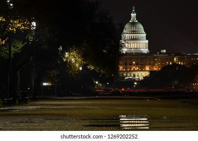 Washington DC at night - United States Capitol and reflection on rain puddle