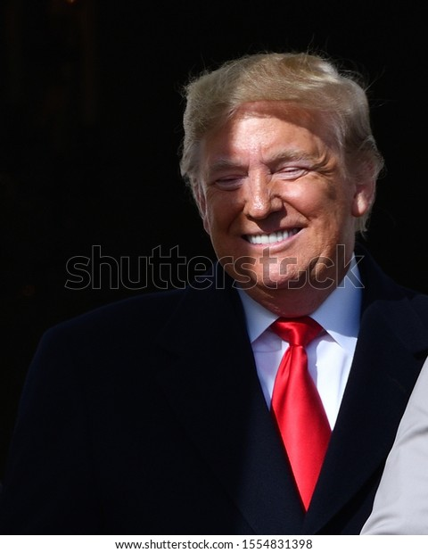 """WASHINGTON, DC - NOVEMBER 04, 2019: """"Half Moon Trump"""", US President stands in shadows on the Balcony at the White House South Lawn ceremony for the Washington Nationals World Series Win."""