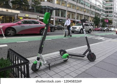 WASHINGTON, DC - OCT. 11, 2018: Two dockless electric scooters parked, SKIP scooter rider rides in background., downtown, DC. Lime-S and Bird scooters among several scooter companies in Washington