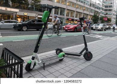WASHINGTON, DC - OCT. 11, 2018: Two dockless electric scooters parked, bike riders in bikelane in background, scooter rider on right. Lime and Bird scooters among several scooter companies in DC