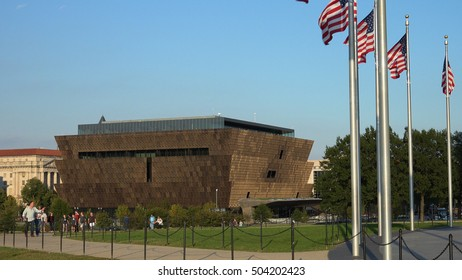 WASHINGTON, DC - OCT. 2016: Museum of African American History and Culture, American flags. Tourists stroll, flags flutter at Washington Monument grounds.  Museum in distance.  Opened Sept. 2016