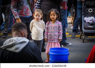 WASHINGTON, DC - OCTOBER 13, 2018: Two young girls watch a drummer with fascination during the H Street Festival in Washington DC