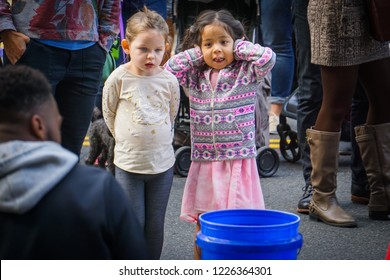 WASHINGTON, DC - OCTOBER 13, 2018: Two girls watch a street musician during the H Street Festival in Washington DC. One covers her ears because it's too loud.