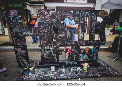WASHINGTON, DC - OCTOBER 13, 2018: People draw with chalk on a sign during the H Street Festival in Washington DC