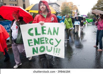 "WASHINGTON, DC - OCTOBER 24: An environmental activist holds a sign saying, ""Clean Energy Now"" during the International Day of Climate Action on October 24, 2009 in Washington, DC"