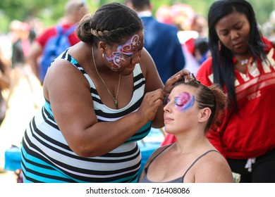 """Washington, DC - September 16, 2017: A woman gets her face painted during a protest in support of President Donald Trump, deemed the """"Mother of all Rallies"""" (MOAR)."""