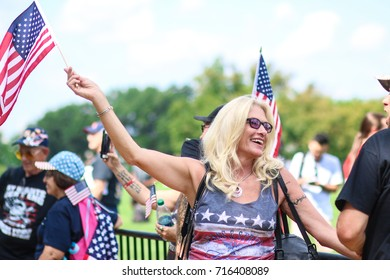 """Washington, DC - September 16, 2017: A Trump supporter waves the American flag during a rally in support of President Donald Trump, deemed the """"Mother of all Rallies"""" (MOAR)."""