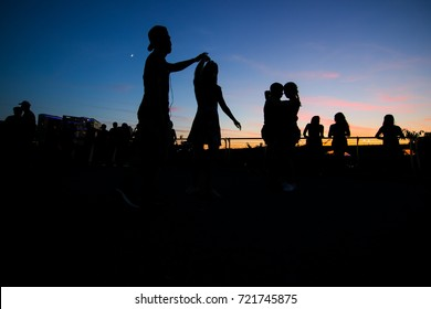 Washington, DC - September 24, 2017: Latin dancers gather at the Georgetown Waterfront to practice their salsa, bachata, zouk and kizomba outside with the sunset behind them.