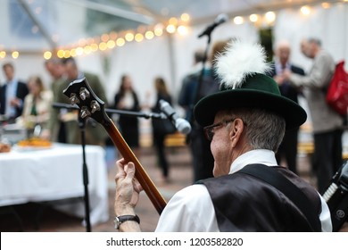 Washington, DC - September 27, 2018: A man in a German band plays German folk music for guests at an Oktoberfest themed networking event.