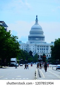 Washington DC, Washington / United States - August 25th 2018: View to Capitol Building from street level with people and cyclist in foreground