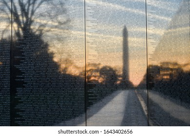 Washington DC / United States - December 1 2014: Vietnam Veterans Memorial wall and reflection of Washington Monument on it during sunrise