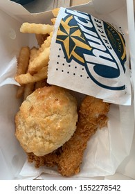 Washington, DC / US - November 06, 2019: Three piece deep fried chicken tender meal with a honey butter biscuit and french fries on wax paper in a basket to go