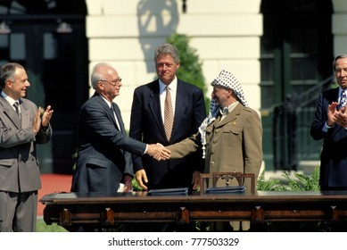 Washington DC. USA, 13th September, 1993 Yitzhak Rabin of Israel and Yasser Arafat of the PLO shake hands at the White House South Lawn after signing the Peace Accords, President Bill Clinton looks on