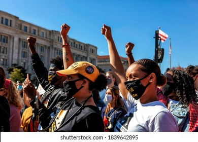 Washington, DC, USA - 17 October 2020: Local leaders of anti-racist organizations raise their fists in support while a woman from Black Lives Matter DC speaks to the crowd at the Women's March