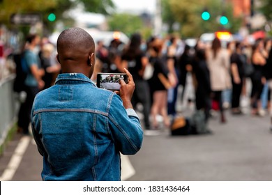 Washington, DC, USA - 26 September, 2020: Bystander taking video of March for Justice while protesters stop on 14th Street.  The March for Justice is a weekly protest against police brutality