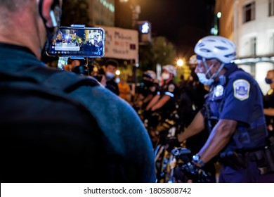 Washington, DC, USA, 27 August, 2020.  A man streams confrontation between  protester and Metropolitan (DC) Police officers live on social media on eve of March on Washington