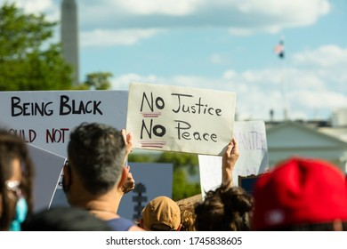 """Washington, DC, USA - 31 May 2020: Protester holds sign""""No Justice No Peace"""" in Front of the White House in a Demonstration over the Death of George Floyd, a black Man who died during a Police Arrest"""