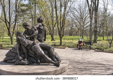 Washington, DC, USA - April 10, 2013: Vietnam Women's Memorial.  A lone tourist sits on a nearby bench to reflect on this historic memorial.