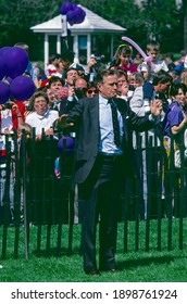 Washington DC, USA, April 16, 1990 President George H.W. Bush blows a whistle to signal the start of the annual Easter Egg Roll on the South Lawn of the White House