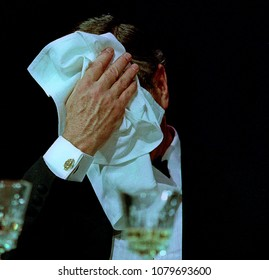 Washington, DC., USA, April 29, 1989 President George H.W. Bush at the annual White House Corrsepondents Association Dinner, laughs at Impressionist Jim Morris,   ends up holding napkin over his face