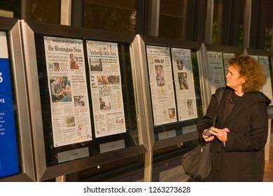 WASHINGTON, DC, USA - APRIL 30, 2008: Woman looks over newspaper front pages, at the Newseum, an interactive museum of news and journalism.