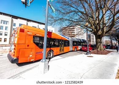 Washington DC, USA - April 5, 2018: Capital red orange bus Metrobus metro big public transport vehicle waiting for passangers on Virginia avenue street in city, wide angle, road
