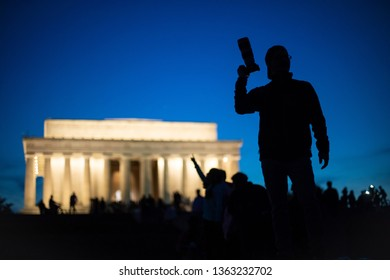 Washington, D.C. / USA - April 6, 2019: The silhouette of a young male photographer with a telephoto zoom lens in front of the Lincoln Memorial, a popular monument among tourists on the National Mall.