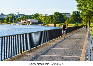 Washington DC, USA - August 15, 2013: Man jogging by Potomac river with skyline of Georgetown on sidewalk