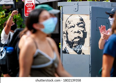 Washington, DC, USA - August 22, 2020.  Protesters walk past a portrait of John Lewis during the Defund the Police March in Columbia Heights, sponsored by DC Protests