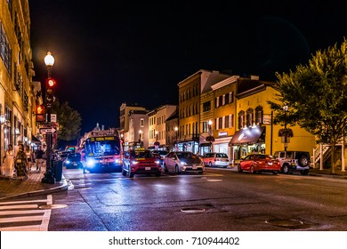 Washington DC, USA - August 4, 2017: Street and shops in Georgetown neighborhood with traffic at night illuminated by golden lights