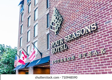 Washington DC, USA - August 4, 2017: Four Seasons hotel with brick architecture in Georgetown neighborhood exterior with entrance and international flags
