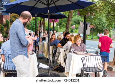 Washington DC, USA - August 4, 2017: People sitting at outside area patio tables on M street in Georgetown Das Ethiopian Cuisine restaurant in evening