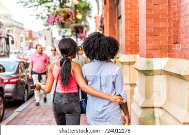 Washington DC, USA - August 4, 2017: Two girlfriends walking in evening embracing, arms around body in downtown Georgetown neighborhood