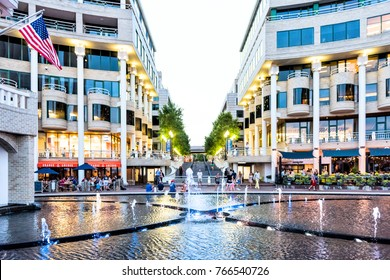 Washington DC, USA - August 4, 2017: Closeup view of colorful fountain at night in Georgetown Waterfront Park Harbor with restaurants and people walking at waterfront park