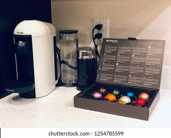 WASHINGTON DC, USA - DECEMBER 09, 2018: A nespresso Vertuo coffee machine by Breville on the kitchen counter accompanied with a eclectic milk frothed and Nespresso Vertuo coffee pods.