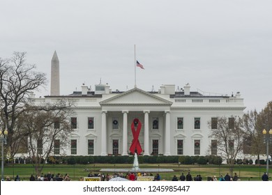 Washington, DC / USA - December 1, 2018: a red ribbon hangs at the White House for the 30th anniversary of World AIDS Day, and the flag is at half staff in honor of President George H.W. Bush.