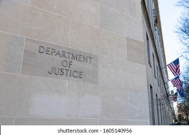 WASHINGTON, DC, USA - December 11, 2019: Department of Justice text on the side of their HQ in Washington, D.C. - American flags in the background.
