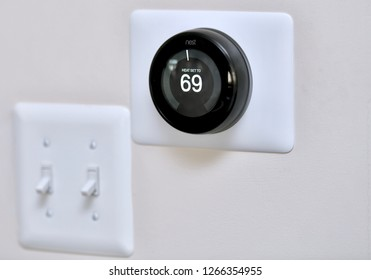 WASHINGTON DC, USA - DECEMBER 24, 2018: A nest learning smart thermostat on the wall of a residential home.