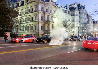 Washington DC, USA - December 28, 2017: Eisenhower Executive Office Building in evening, holiday winter lights illuminated road street with traffic cars, hot steam vapor coming from manhole, red taxi