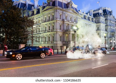 Washington DC, USA - December 28, 2017: Eisenhower Executive Office Building in evening, holiday winter lights illuminated road street with traffic cars, hot steam vapor coming from manhole