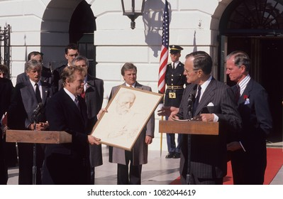 Washington, DC., USA, February 20, 1990 President of Czechoslovkia Vaclav Havel presents US. President George H.W. Bush with a framed picture during ceremony outside the South Diplomatic entrance